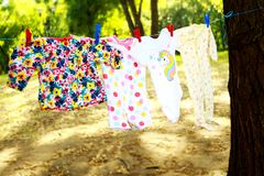 Baby clothes hanging on rope. Baby clothes drying on rope. the clothes are drying for the little girl, the colored dress, the overalls and the blouse are hung on stock photos