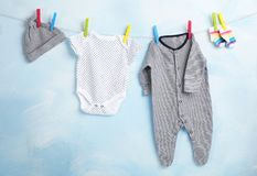 Baby clothes hanging on rope. Near color wall stock images