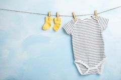 Baby clothes hanging on rope near color wall. Space for text royalty free stock images
