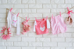 Baby clothes hanging on the wall stock photos