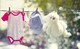 Baby clothes, hat and teddy hanging on the clothesline Royalty Free Stock Images