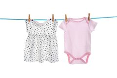 Baby clothes on laundry line. Against white background stock photos