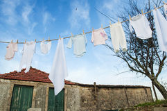 Baby clothes on line outside in rural garden Royalty Free Stock Photos