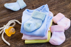 Baby clothes. Newborn baby clothes with pink and blue socks on wooden background stock photography