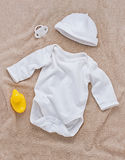 Baby clothes and pacifier on soft towel Stock Image
