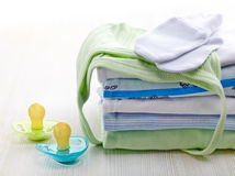 Baby clothes. Pile of blue and green baby clothes and pacifiers on white wooden background royalty free stock photo