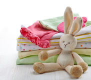 Baby clothes. Pile of colorful baby clothes and toy on white wooden background Royalty Free Stock Photography