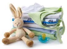 Baby clothes. Pile of green and blue baby clothes, pacifier and toy isolated on white background Royalty Free Stock Photo