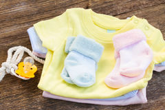 Baby clothes. Pile newborn baby clothes with pacifier on wooden background royalty free stock photos