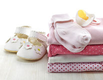 Baby clothes. Pile of pink baby clothes and pacifier on white wooden background royalty free stock photo