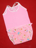 Baby clothes. Pink baby clothes on brown background stock images