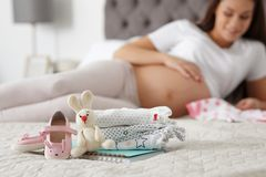 Baby clothes prepared for maternity hospital. And pregnant woman on background royalty free stock image
