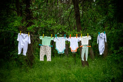 Baby clothes on rope. With green forest in the background Stock Photography