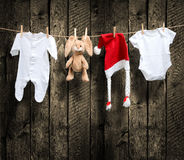 Baby clothes and santa hat on a clothesline Stock Image