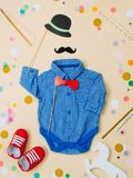 Baby clothes and shoes with paper hat, mustache and the bow tie. Baby shower party concept. Baby clothes and shoes with paper hat, mustache and the bow tie on stock image