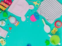 Baby clothes, soother, spoon, brush and toys over green backgrou. Baby accessories background: baby`s clothes, soother, spoon, brush and toys over green Stock Photography