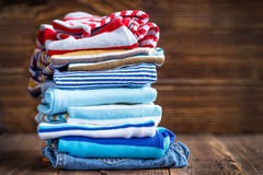 Baby clothes. Stack on a wooden table royalty free stock images