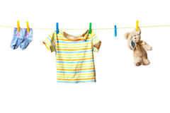 Baby clothes and a teddy bear. Drying on a rope isolated on white background Royalty Free Stock Image