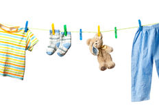 Baby clothes and a teddy bear. Drying on a rope isolated on white background Stock Photo