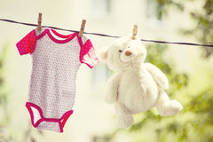 Baby clothes and teddy bear hanging on the clothesline Royalty Free Stock Photography