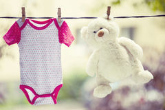 Baby clothes and teddy bear hanging on the clothesline. Family concept Stock Photography