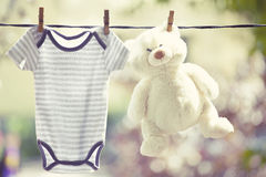Baby clothes and teddy bear hanging on the clothesline. Family concept Royalty Free Stock Images