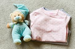 Baby clothes. Teddy bear toy near a Baby clothes on a baby `s bed royalty free stock images