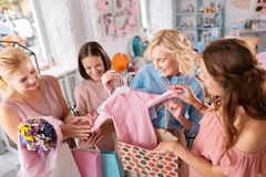 Three guests showing pregnant woman little pink baby clothes. Baby clothes. Three friendly guests showing pregnant women little pink baby clothes while coming to stock photography