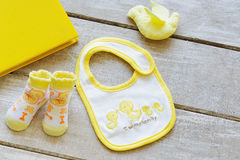 Baby clothes top view. Top view bright yellow trendy look of baby clothes and stuff royalty free stock photo