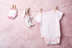 Baby clothes and toy hanging on rope. Near color wall. Space for text royalty free stock images