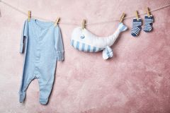Baby clothes and toy hanging on rope. Near color wall. Space for text stock photos