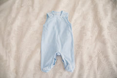 Baby clothes on a white bed Stock Photography
