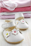 Baby clothes. White baby shoes and pile of pink clothes on white wooden background stock photography