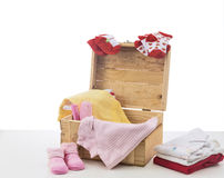 Baby clothes on wood box. Isolated on white Stock Image