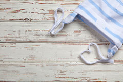 Baby clothes on wooden background Stock Photos