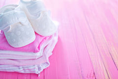 Baby clothes. On the wooden table royalty free stock photography