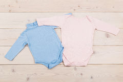 Baby clothes on wooden table Royalty Free Stock Images