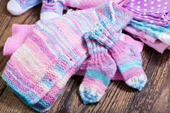 Baby clothes on wooden table. Various baby clothes on wooden table royalty free stock images