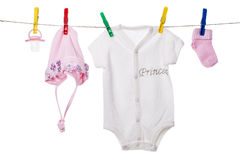 Baby clothing hanging on the clothesline. On a white background Stock Images