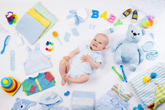 Baby with clothing and infant care items Stock Photos