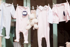 Baby clothing and teddy bear in window Royalty Free Stock Image
