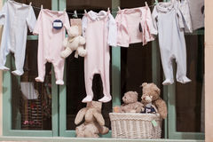 Baby clothing and teddy bear in window Royalty Free Stock Photos