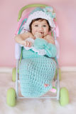 Baby in cocoon. Three months old little baby girl sitting in a toy stroller Stock Images