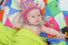 Baby with colorful hat and quilt. Head and shoulders portrait of infant wearing a Peruvian knit hat. Colorful patchwork quilt background, horizontal layout Stock Images