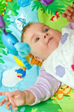 Baby on colorful mat. Cute baby girl lying on colorful education mat Stock Photo