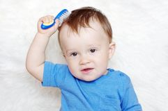 Baby combs hair. Baby age of 11 months combs hair Stock Photo