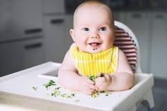 Baby' comida de s primer a alimentar Imagenes de archivo
