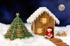 Baby composite with christmas candy house. Composite image of a newborn baby in front of a christmas gingerbread house in a snow landscape royalty free stock photo