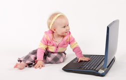 Baby and Computer. Image of the girl playing with laptop computer Stock Photos