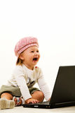 Baby computer genious. Adorable caucasian baby girl toddler wearing a cute pink hat sitting on the floor working on a laptop computer laughing Stock Photos